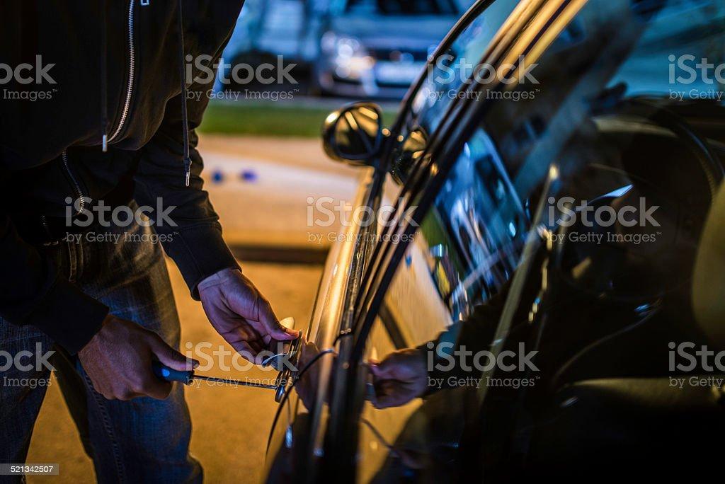 Car Thief Using a Screwdriver to Brake into a Car stock photo