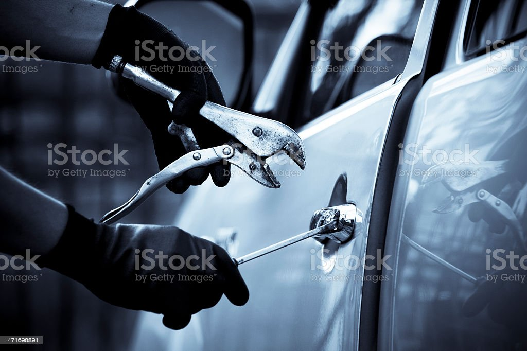 Car thief using a tool to break into car. stock photo