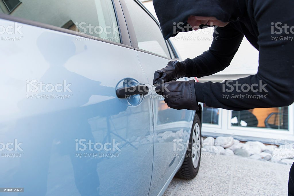 Car thief using  special tools to brake into a car stock photo
