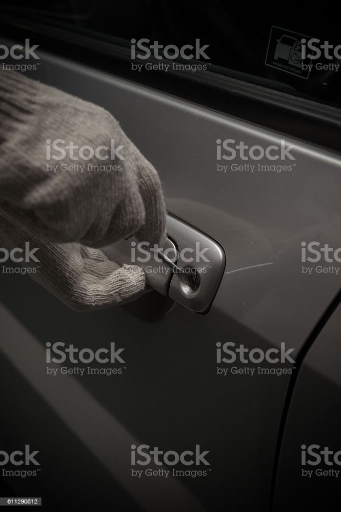 car thief with glove trying to open a vehicle door stock photo