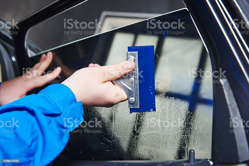 car tinting. Automobile mechanic technician applying foil stock photo