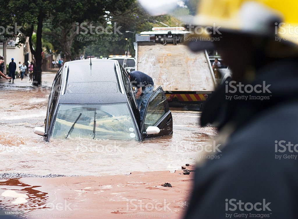 Car tips into pothole in flooded street, front view stock photo