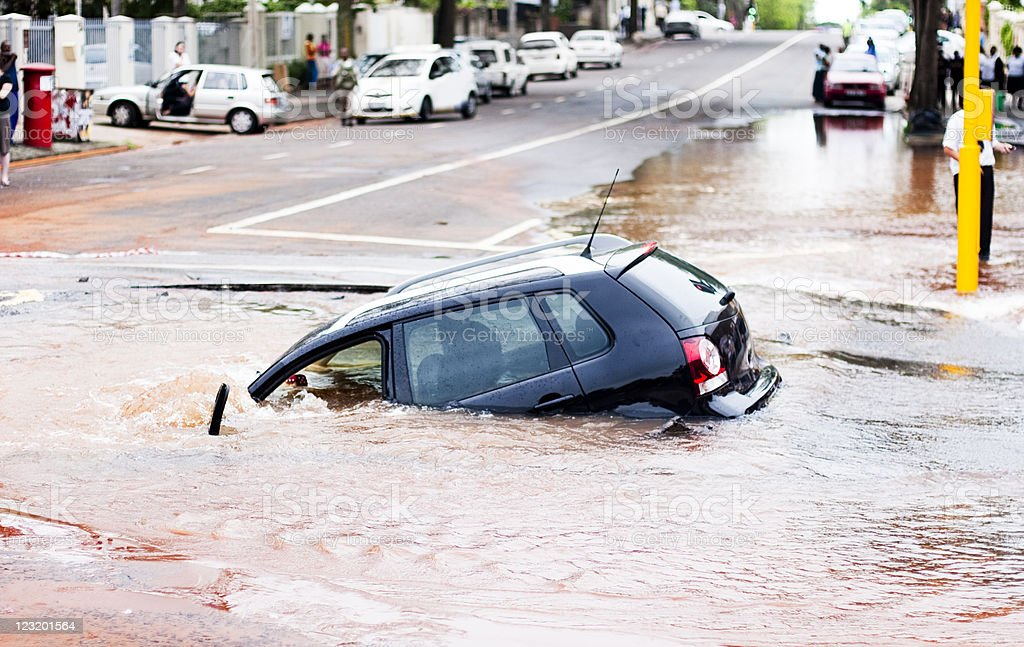 Car tips into pothole in flooded street, side view stock photo