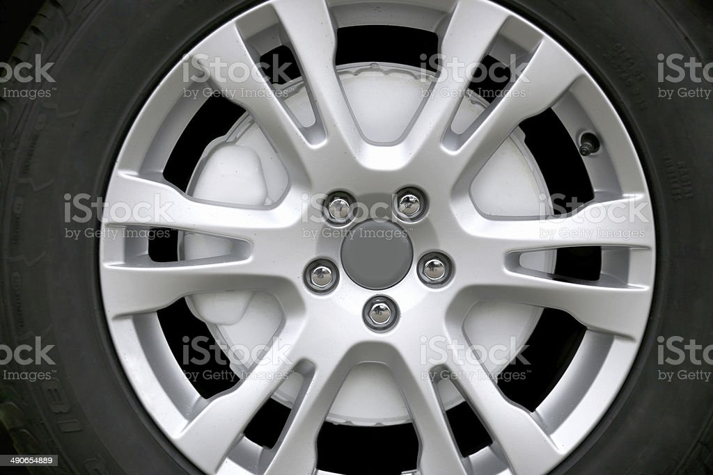 Car tire on six spoke alloy wheel and brake cover stock photo
