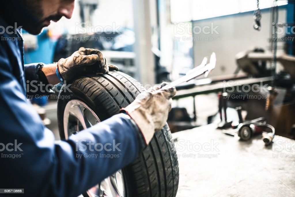 car tire repairmen with caliber stock photo