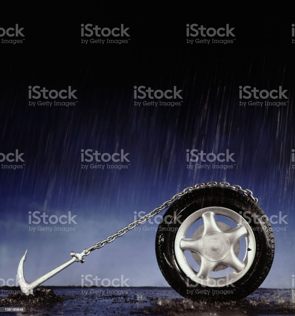Car tire with chain anchored to the ground in the rain stock photo
