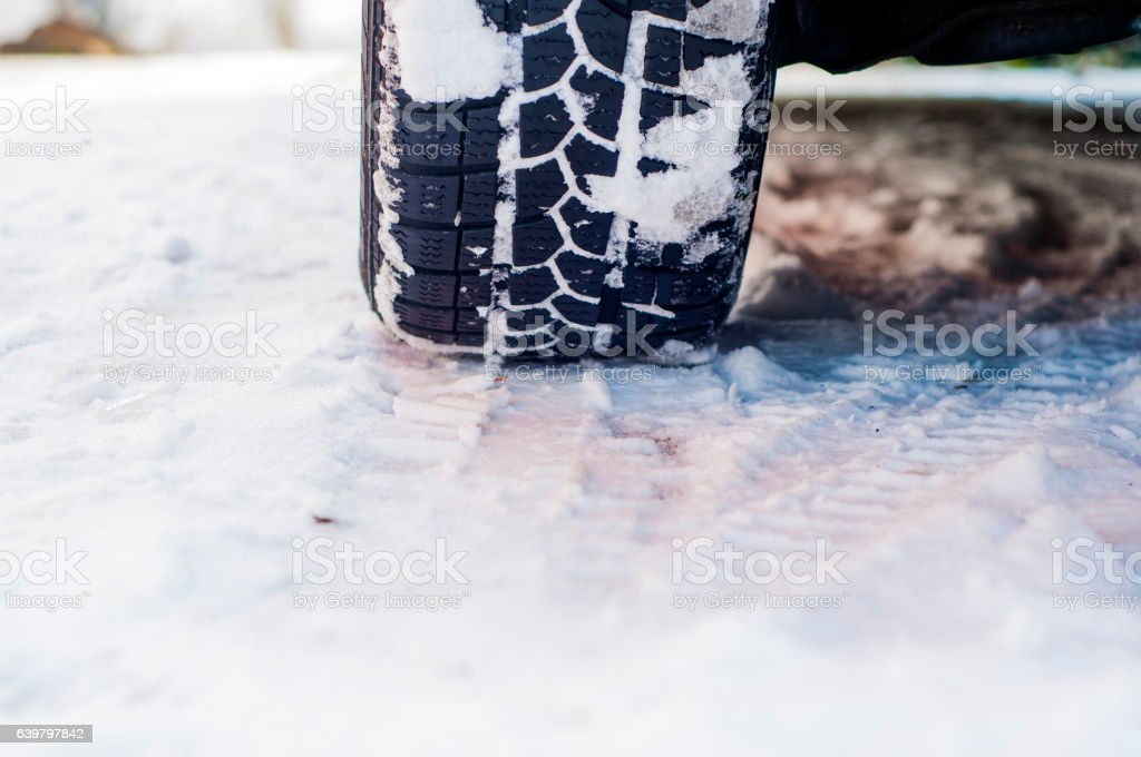 Car tires on winter road covered with snow. stock photo