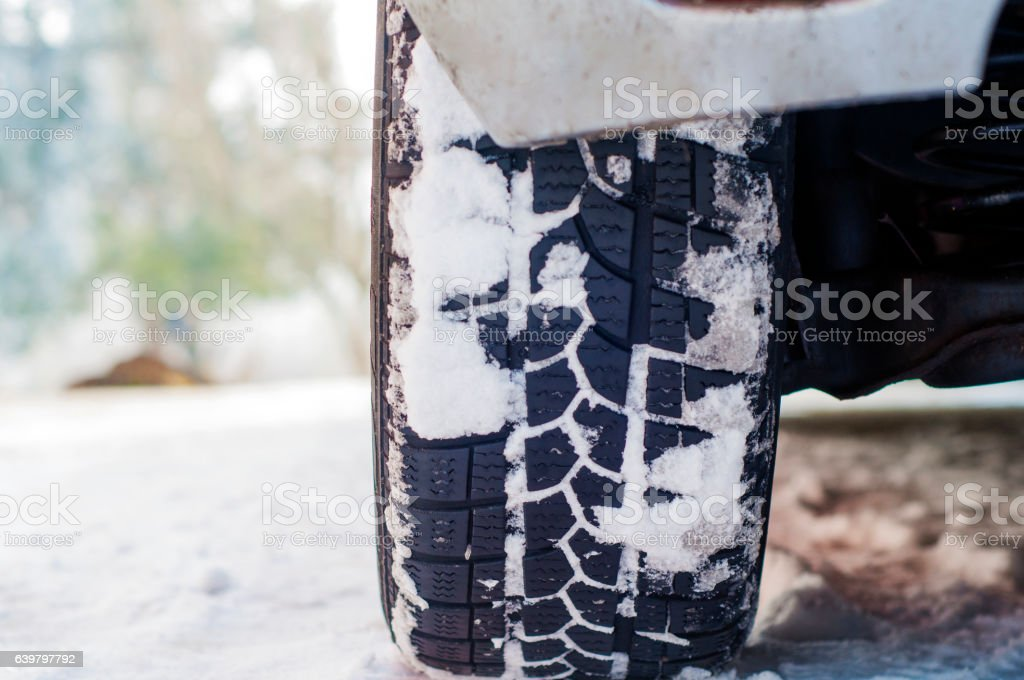 Car tires on winter road covered with snow. Vehicle, snowy stock photo