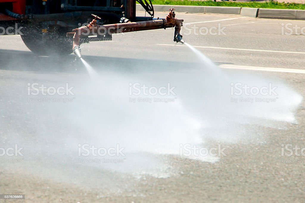 car to watering of roads and highways stock photo