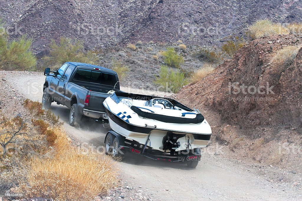 A car towing a boat through the dirt road stock photo