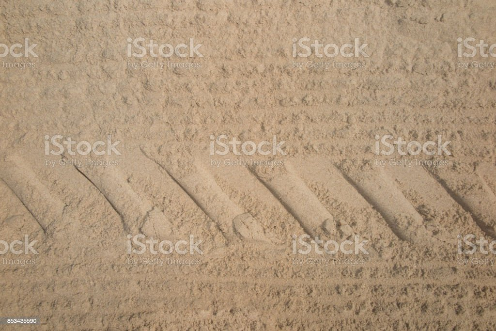 Car tracks in the sand on summer at the beach background stock photo