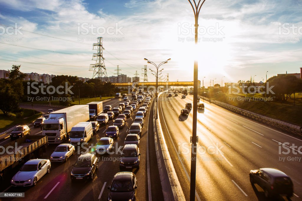 Car traffic on the highway at sunset stock photo