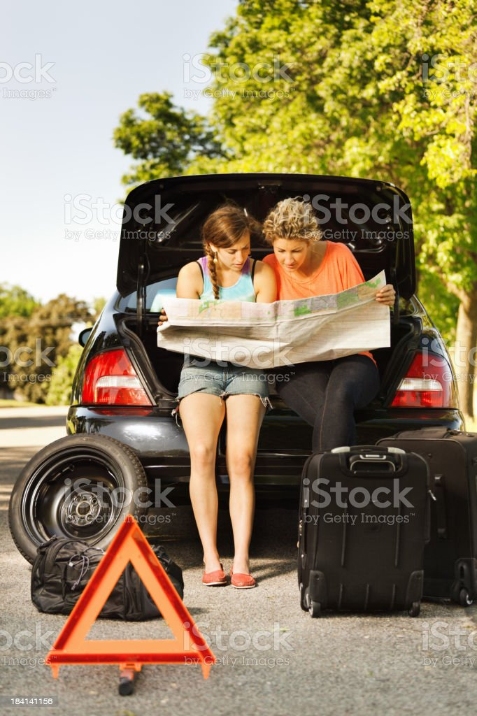 Car Trouble Destressed Travelers Looking at Map Seeking Emergency Service royalty-free stock photo
