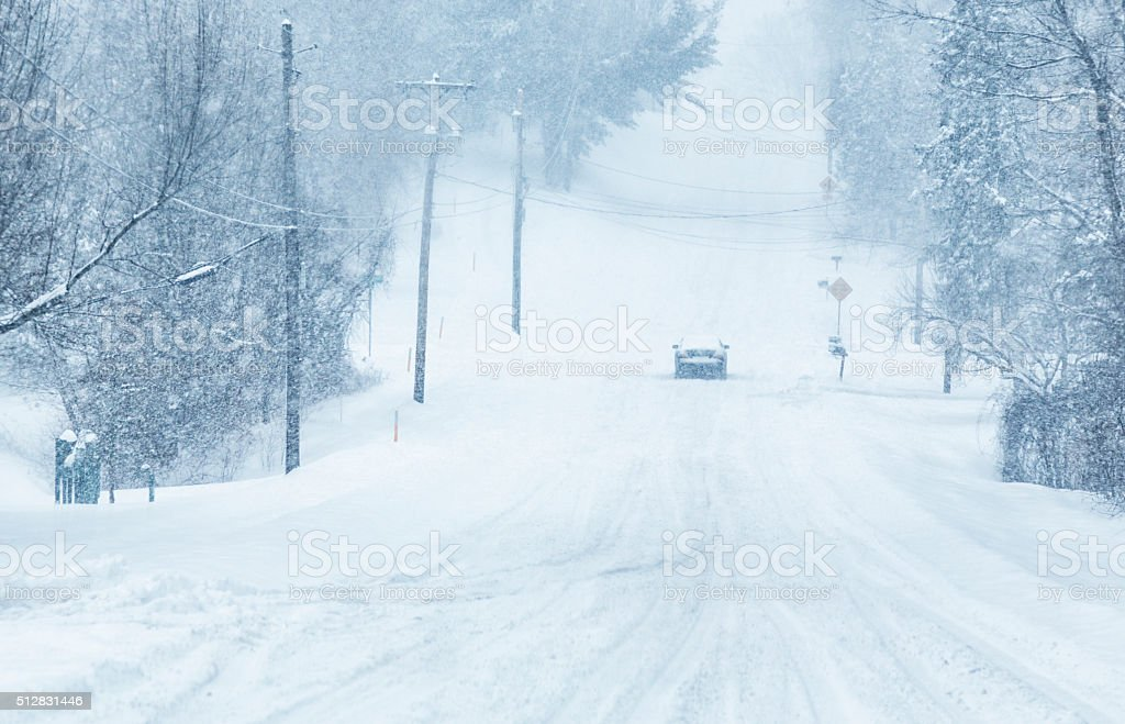 Car Unable to Climb Slippery Hill During Blizzard Snow Storm stock photo