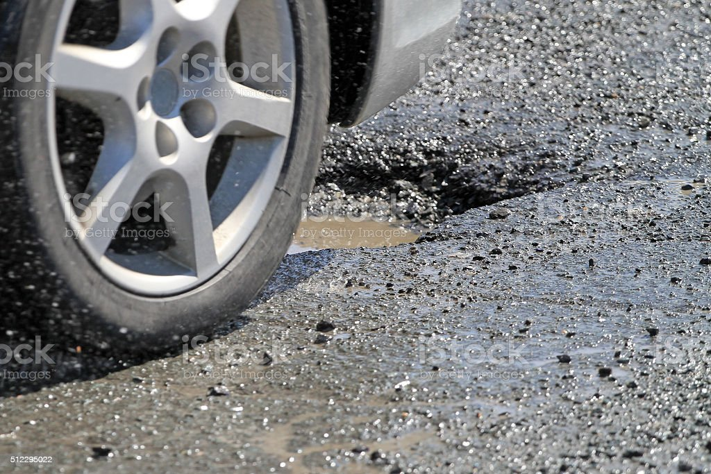 Car Wheel Moments Before Hitting  Pothole On City Street stock photo