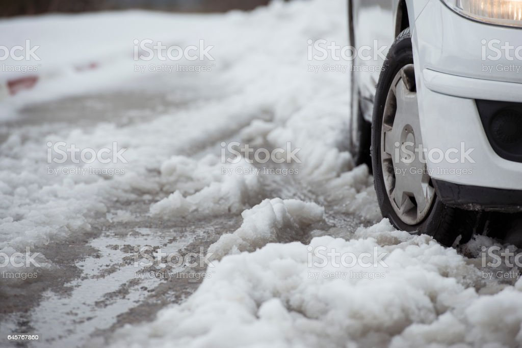 Car wheels on  road. Dangerous section of snowy road. stock photo