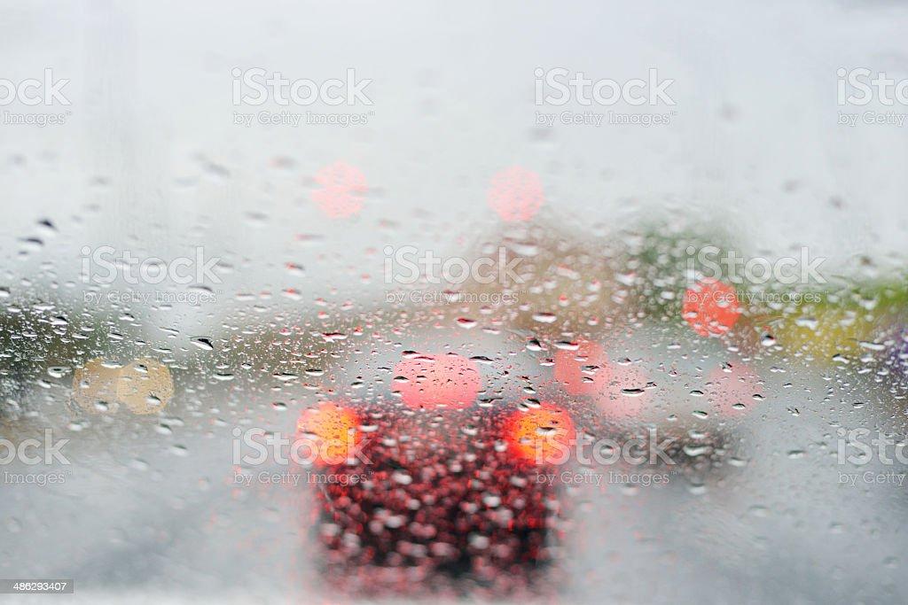 Car windshield in traffic and rain stock photo