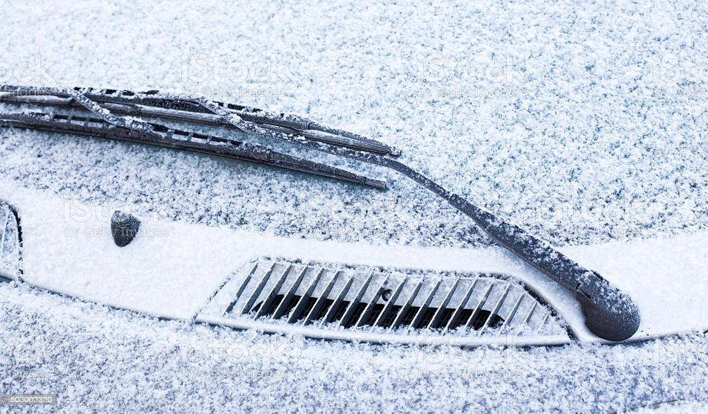 Car wipers and windscreen covered with snow stock photo