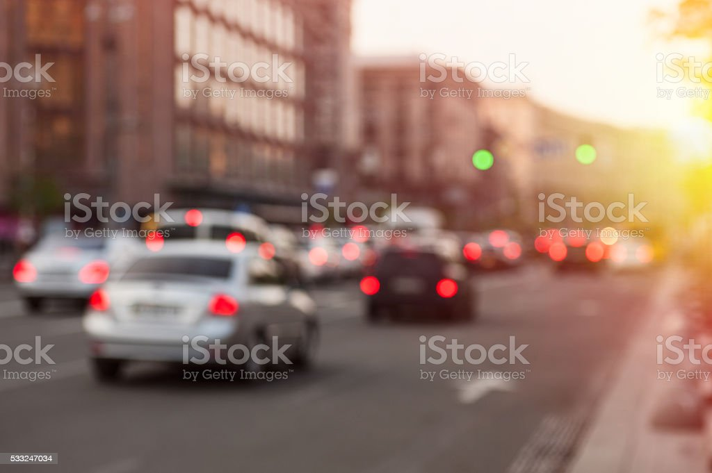 car with lights at evening on city road. Blurry stock photo