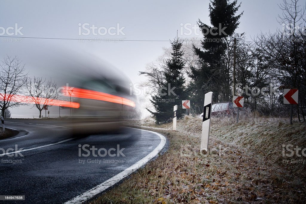 Car with red brake lights is passing a curve stock photo