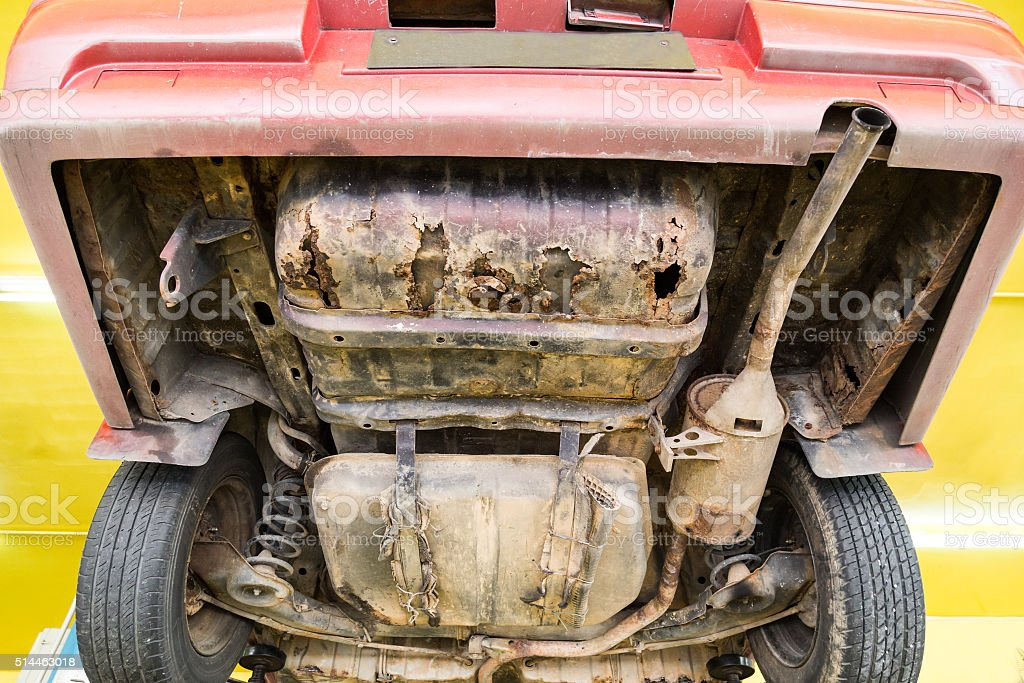 Car with rusty, damaged, corroded undercarriage at workshop for stock photo