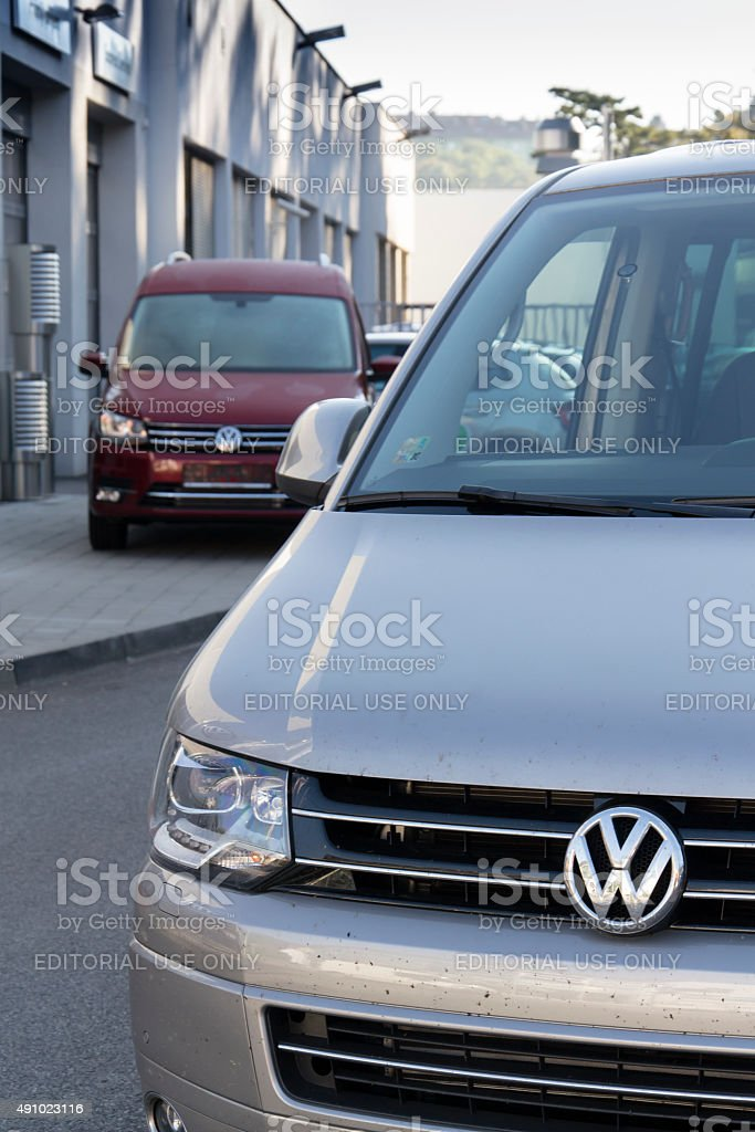 Car with Volkswagen logo in front of dealership building stock photo