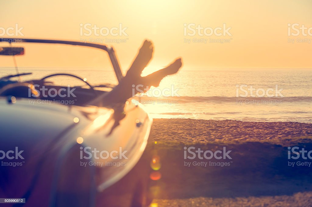 Car with womans feet hanging out of the window stock photo