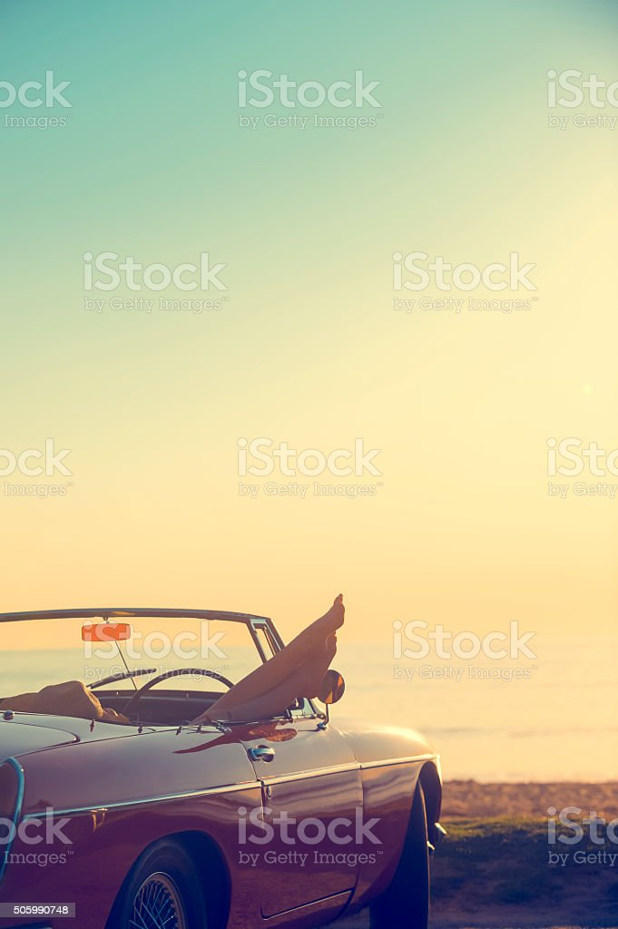 Car with womans feet hanging out of the window. stock photo