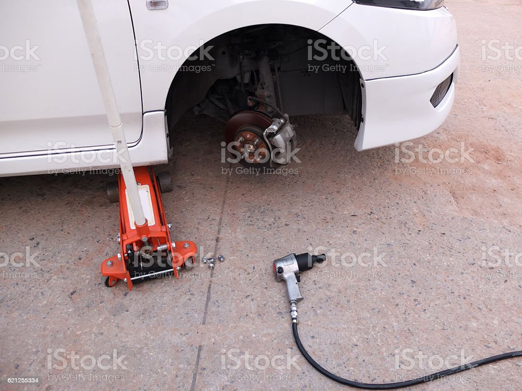 Car without tire at jack in service stock photo