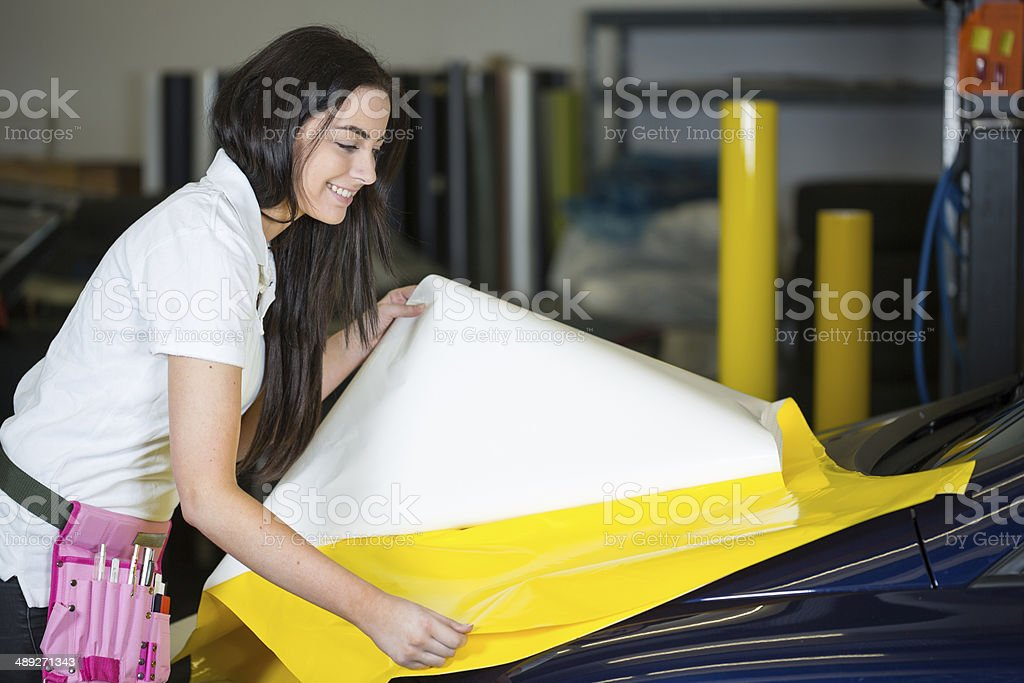 Car wrapper preparing foil to wrap a vehicle stock photo
