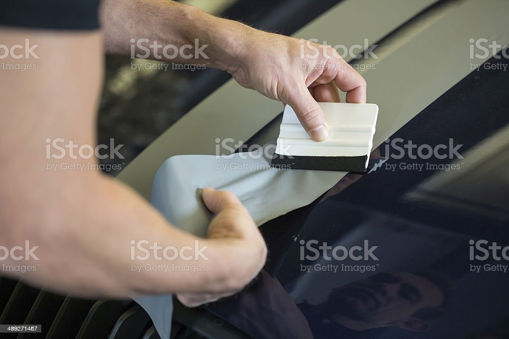 Car wrapper straightening foil with a squeegee stock photo