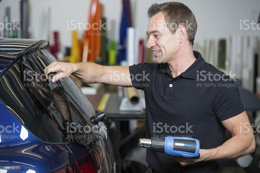 Car wrapper tinting vehicle window with foil stock photo