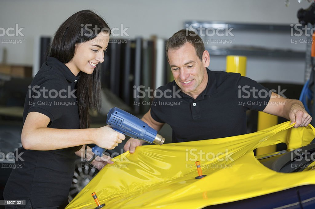 Car wrappers using heat gun to prepare vinyl foil stock photo