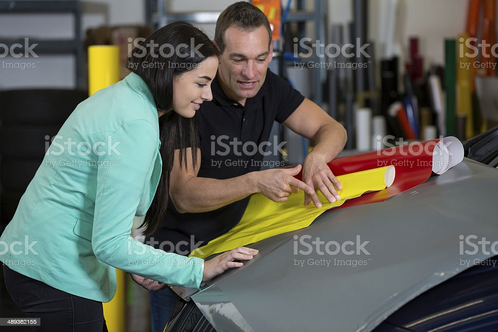 Car wrapping specialist consulting client about vinyl films stock photo