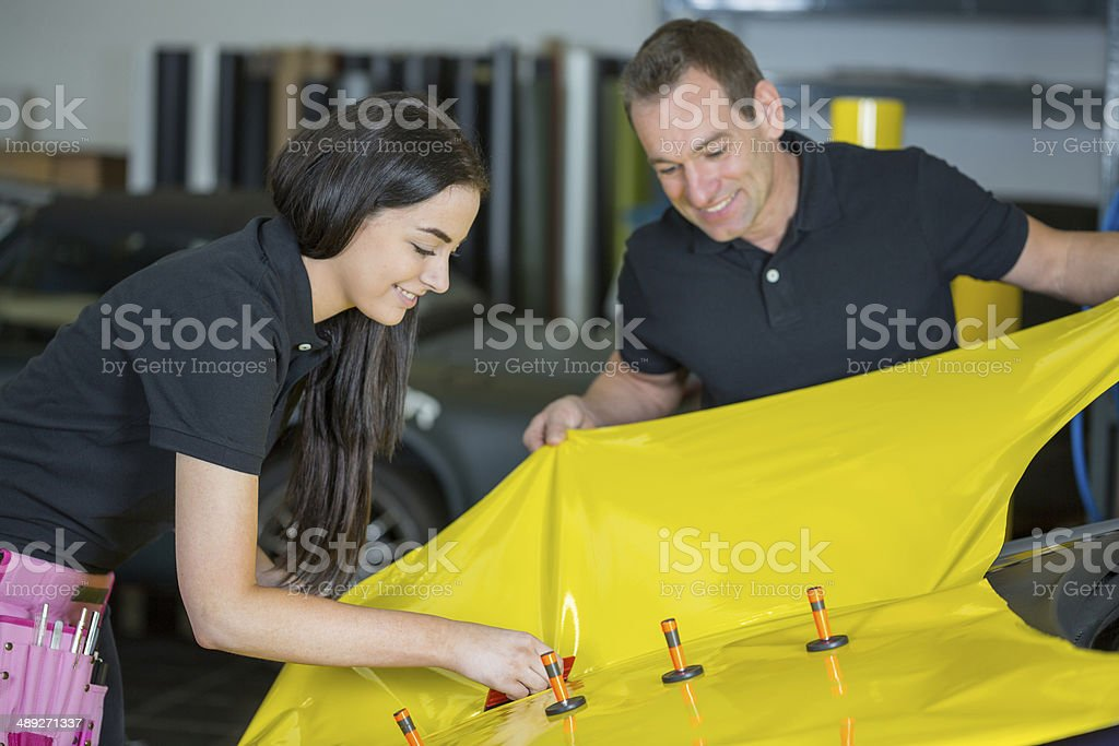 Car wrapping specialists straightening vinyl foil or film stock photo