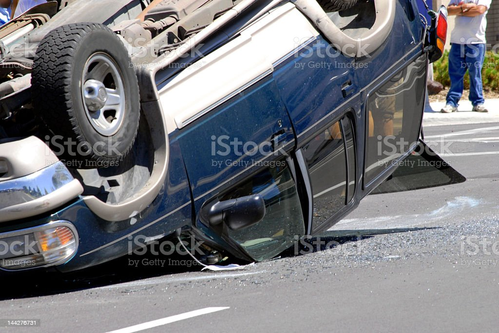 A car wreck with a car upside down on the road stock photo