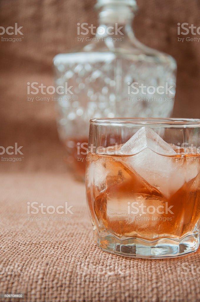 Carafe  glass of whisky, whiskey bourbon on  burlap, sacks  background stock photo