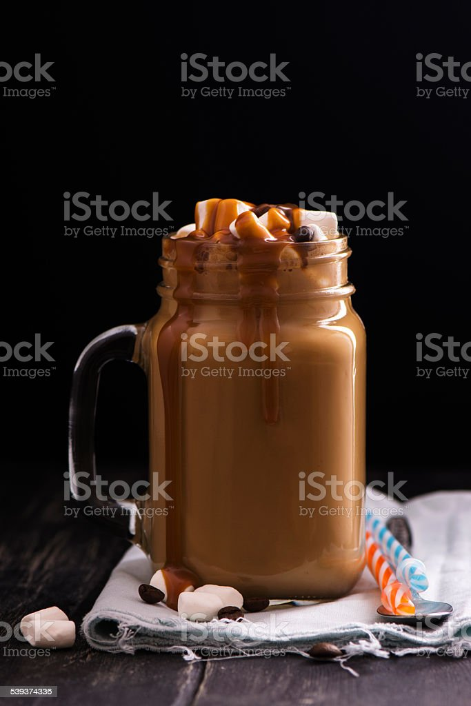 Caramel coffee in mason jar over black wooden table stock photo