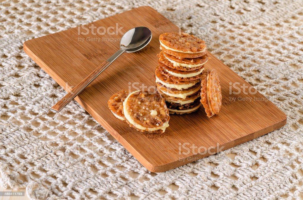 Caramel Florentines cookies on a wooden cutting board stock photo