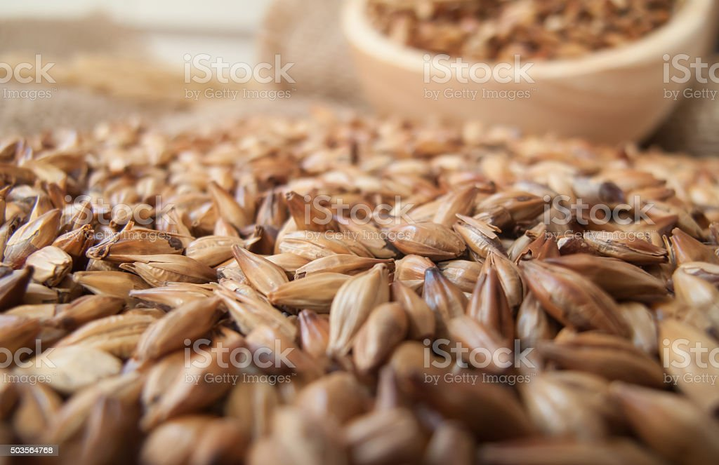 Caramel malt in wooden bowl and on sackcloth stock photo