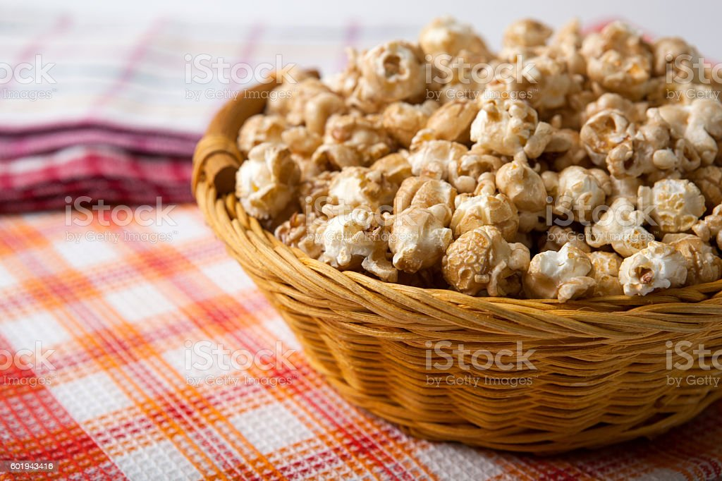 caramel popcorn in a basket on a napkin stock photo