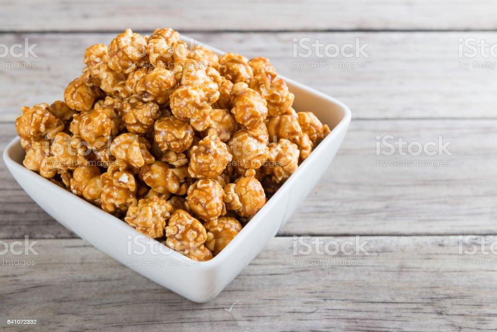 Caramel popcorn on wooden background stock photo