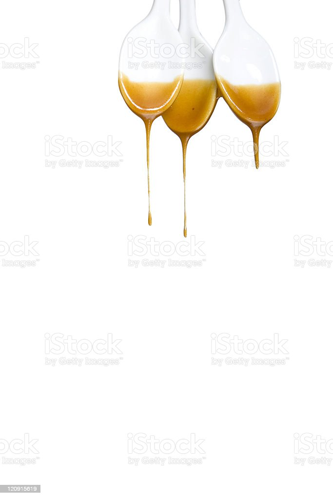 Caramel syrup dripping from spoons stock photo