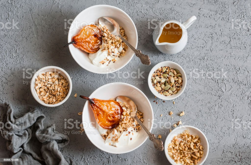 Caramelized baked pears with greek yogurt and granola on a gray background, top view. Healthy breakfast. Flat lay stock photo