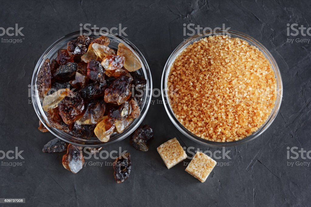 Caramelized sugar and brown cane sugar in glass bowls stock photo