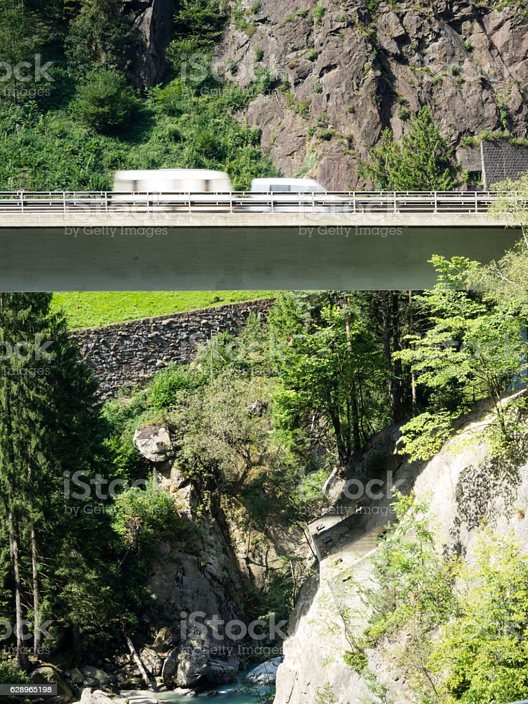Caravan driving on suspended highway / alpine mountain viaduct stock photo