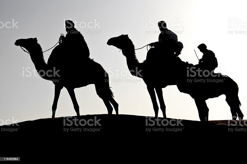 caravan silhouette of three men with dromedaries royalty-free stock photo