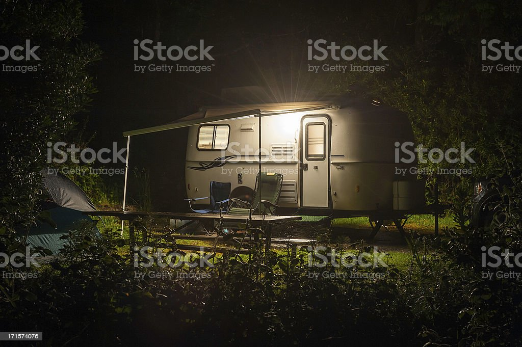 Caravan trailer glowing in forest camp site night stock photo