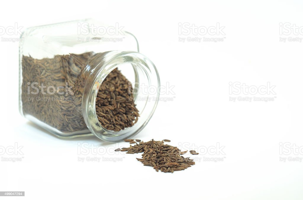 Caraway seeds spilled from glass bottle stock photo
