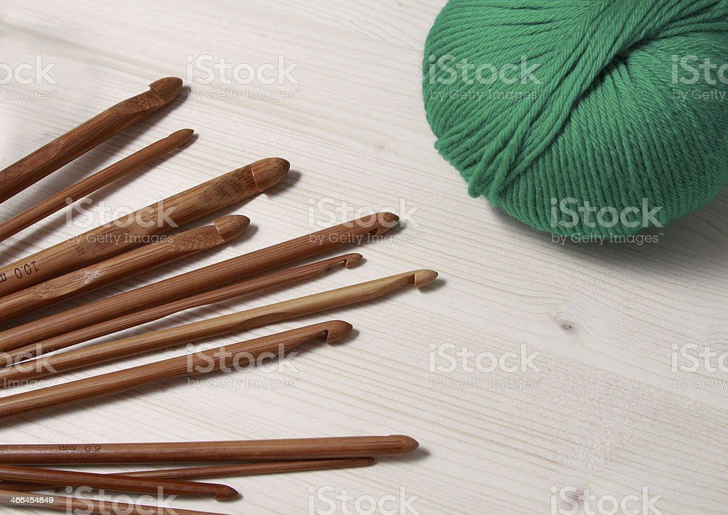 Carbonized bamboo crochet hooks and skein on wooden background stock photo